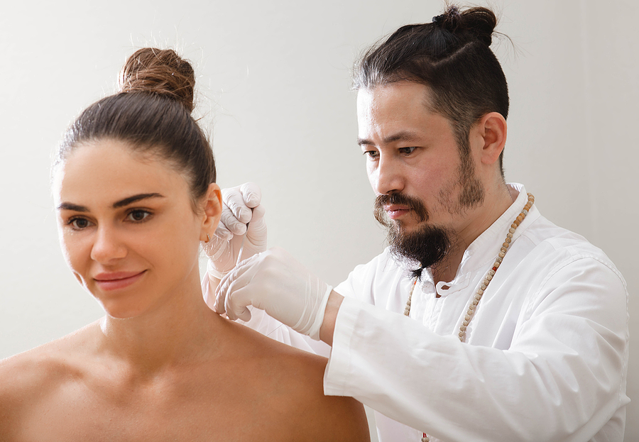 Acupuncture professional doing a treatment to a woman